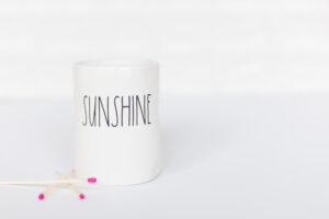 picture of white mug with the word SUNSHINE on it. There are 3 matches to the left of it.